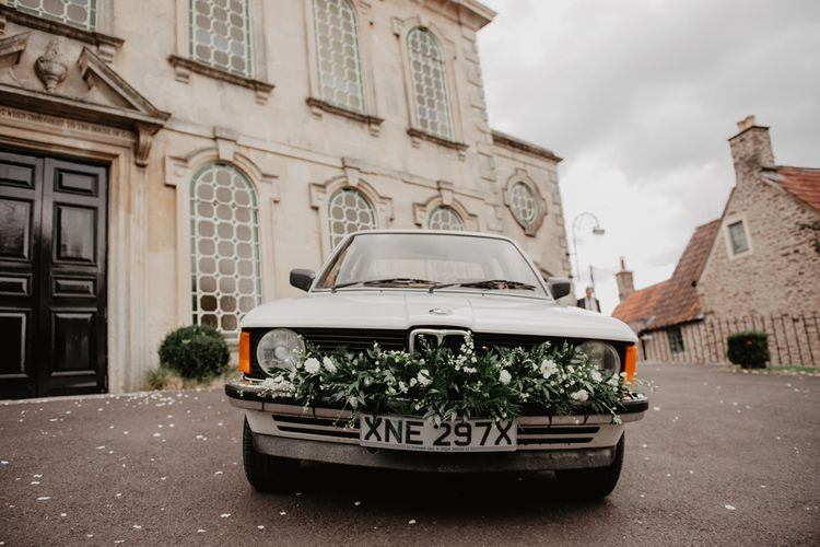 Vintage BMW Wedding Car with White and Green Wedding Flowers Decorating the Bumper