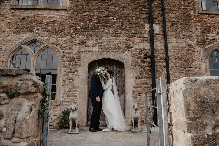 Bride in Homemade Wedding Dress with Long Sleeves and Groom in Navy Reiss Suit Standing Outside Rook Lane Wedding Venue in Somerset