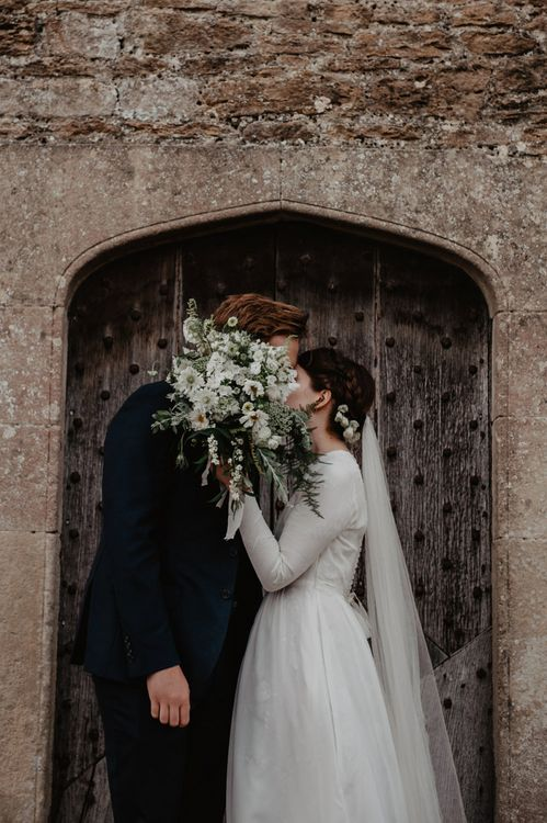 Bride in Homemade Wedding Dress with Long Sleeves and Groom in Navy Reiss Suit Kissing Behind a White and Green Bouquet