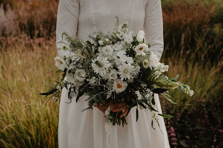 Bride in Homemade Wedding Dress with Long Sleeves Holding White and Green Wedding Bouquet