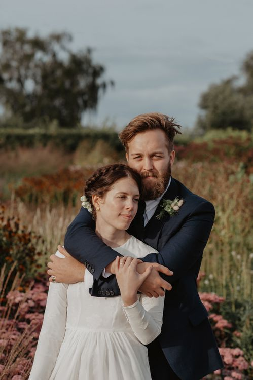 Bride in Homemade Wedding Dress with Long Sleeves and Groom in Navy Reiss Suit Embracing
