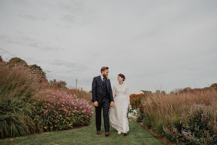 Bride in Homemade Wedding Dress with Long Sleeves and Groom in Navy Reiss Suit Holding Hands
