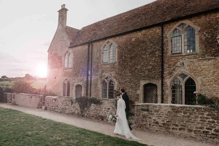 Golden Hour Portrait with Bride in Homemade Wedding Dress with Long Sleeves and Groom in Three-Piece Navy Reiss Suit