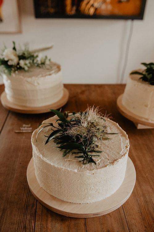 Three Single Tier Wedding Cakes with Green and White Wedding Flower Toppers