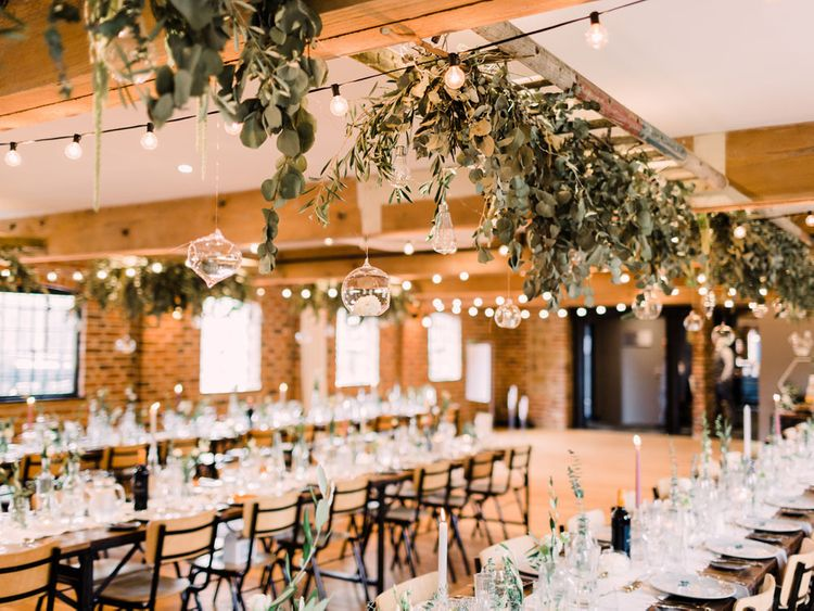 Stunning wedding reception decor with hanging foliage and glass bottles