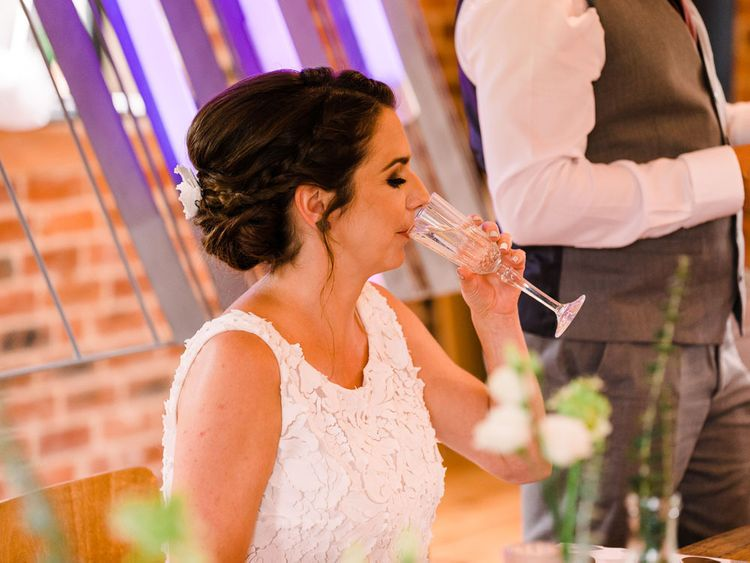 Bride takes a sip of drink as she enjoys her day