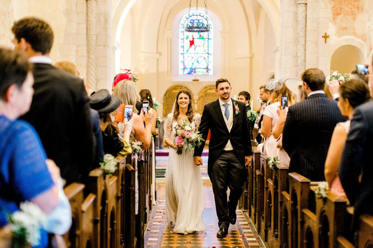 Bride in Dana Bolton Wedding Dress and Groom in Morning Suit Walking Up The Aisle Just Married