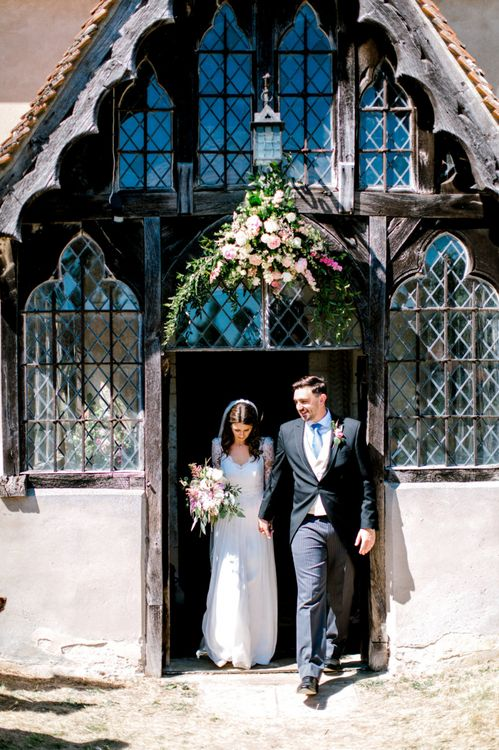 Bride in Dana Bolton Wedding Dress and Groom in Morning Suit Exiting The Church Just Married