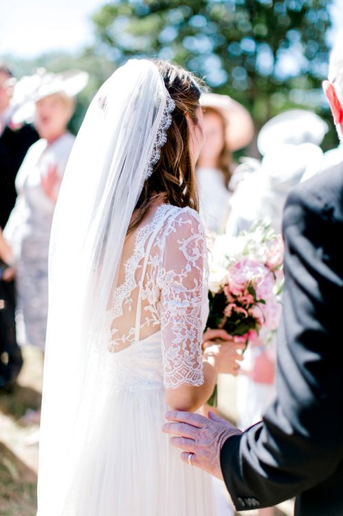 Bride in Dana Bolton Wedding Dress with Lace Detail and Cathedral Length Veil