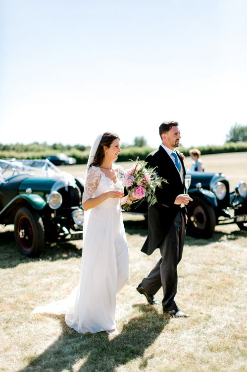 Bride in Dana Bolton Wedding Dress and Groom in Morning Suit Getting Out of Forest Green Vintage Bentley Wedding Car