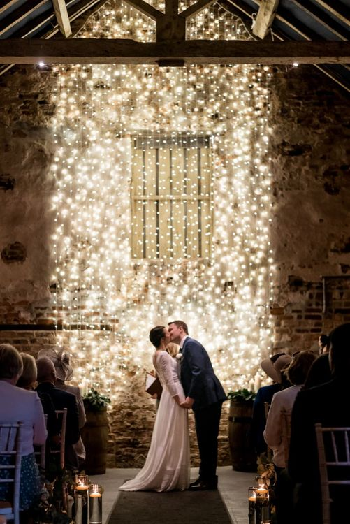 Bride and Groom Kissing at the Altar in Front of a Fairy Light Backdrop