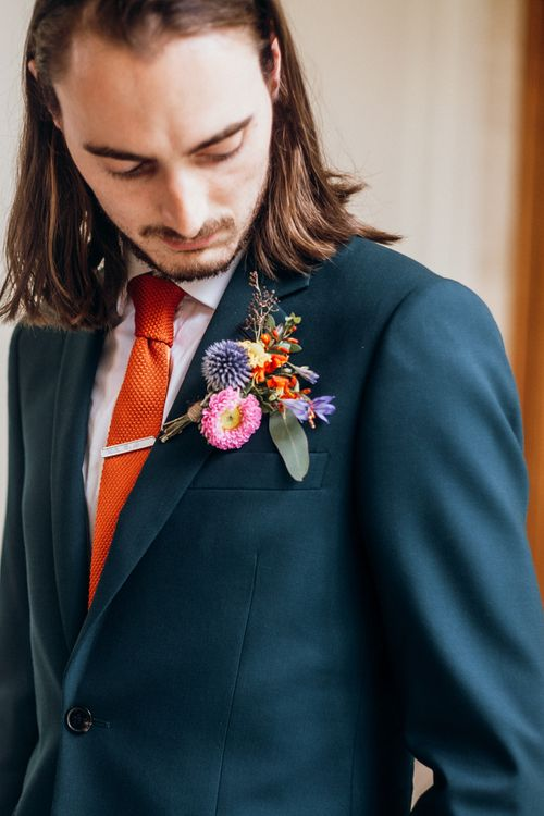 Floral Buttonhole with Orange Tie and Navy Suit