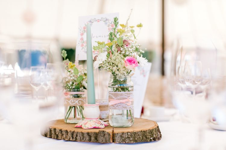 Tree Slice Table Centrepiece with Flower Stems in Jars wrapped in Burlap & Lace