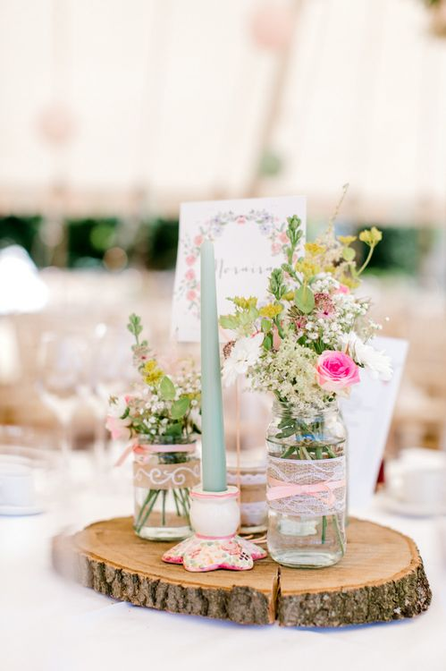 Homemade Wedding Decorations with Glass Jars Wrapped in Hessian and Lace Filled with Flowers
