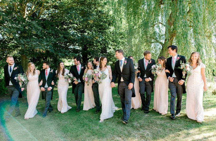 Wedding Party Portrait with Bridesmaids in Pastel Pink Dresses and Groomsmen in Morning Suits