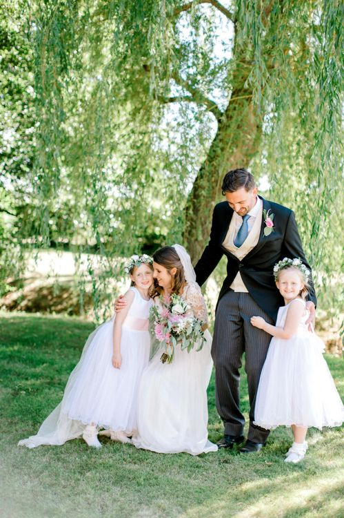 Bride in Dana Bolton Wedding Dress and Groom in Morning Suit with Flower Girls