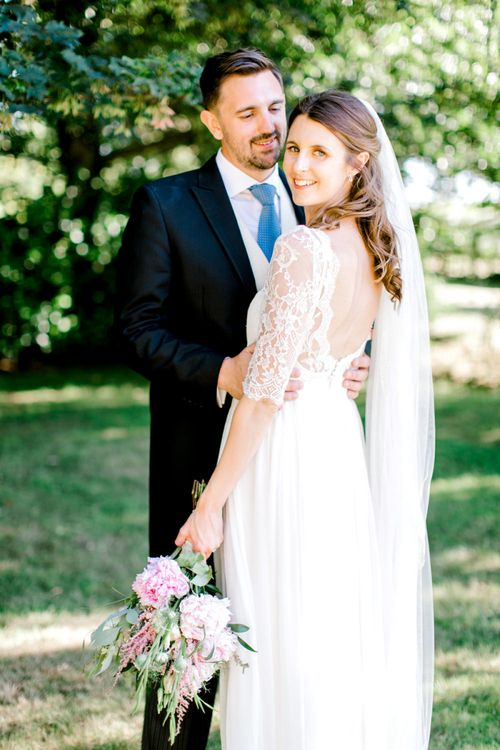 Bride in Dana Bolton Wedding Dress and Groom in Traditional Morning Suit Embracing