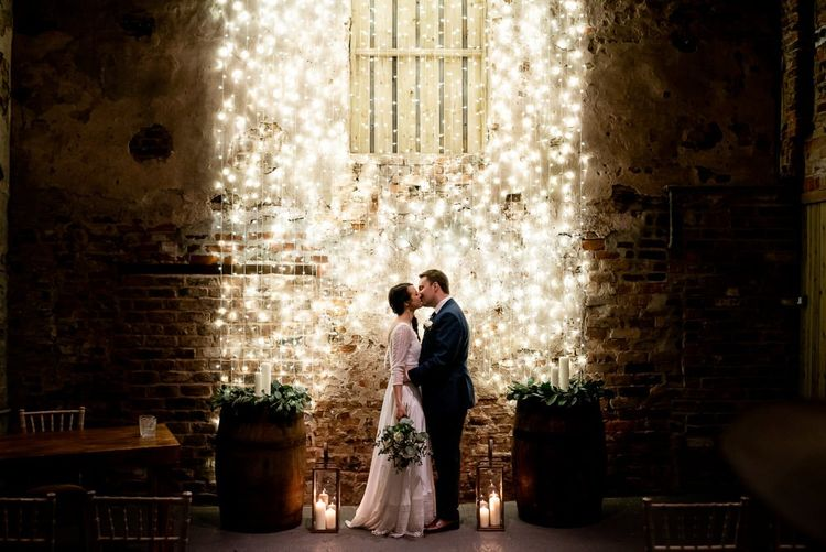 Bride in Rembo Styling Wedding Dress and Groom in Navy Suit Kissing at the Fairy Light Altar