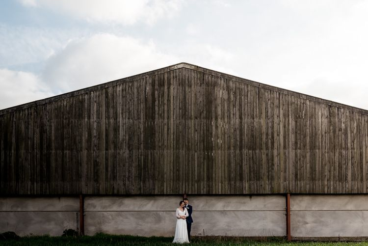 Bride in Rembo Styling Wedding Dress and Groom in Navy Suit Standing in Front of a Barn