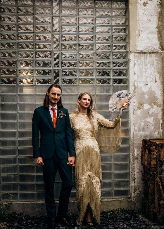 Groom in Navy Suit with Orange Tie and Bride in Gold Wedding Dress