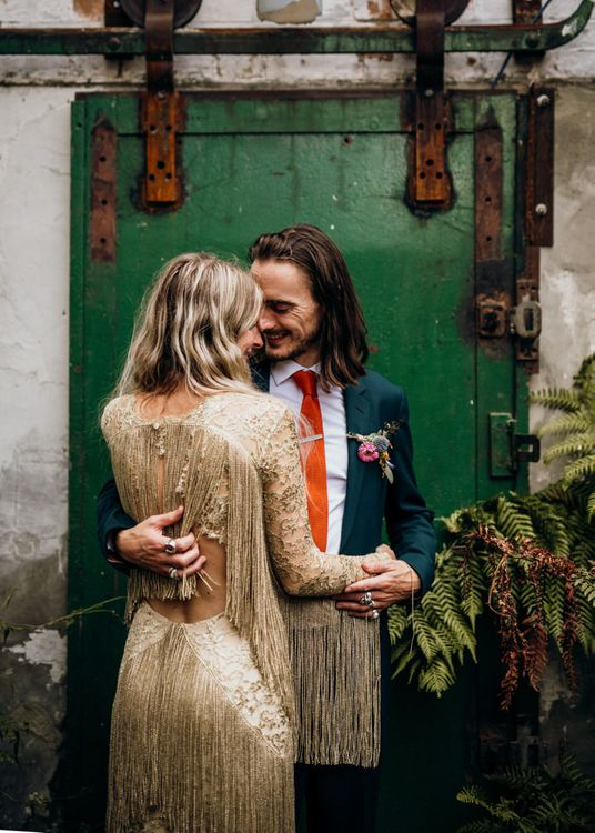 Bride in Gold Fringe Dress with Groom in Navy Suit with Orange Tie and Floral Buttonhole