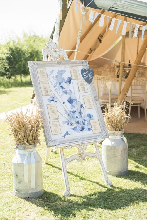 Table Plan in Rustic Frame | Milk Churns | Tipi Wedding Reception at Udimore Village Hall, East Sussex | Morris Minor Wedding Car, Hanging Flowers in Bottles and Town Crier for Village Hall Wedding in Rye | Eleanor Jane Photography