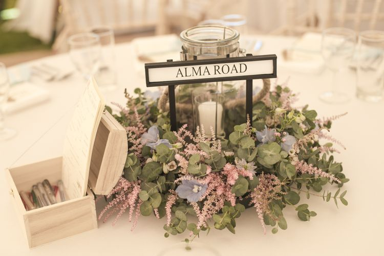 Flower Garland Centrepieces | Pillar Candle | Wedding Advice Cards | Road Sign Table Names | Tipi Wedding Reception at Udimore Village Hall, East Sussex | Morris Minor Wedding Car, Hanging Flowers in Bottles and Town Crier for Village Hall Wedding in Rye | Eleanor Jane Photography