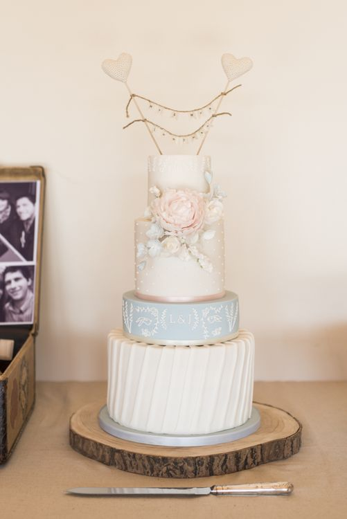 Four-Tier Wedding Cake with Decorative Fondant Icing and Pink Fondant Flower | Mr and Mrs Cake Topper with Heart Sticks and Twine | Morris Minor Wedding Car, Hanging Flowers in Bottles and Town Crier for Village Hall Wedding in Rye | Eleanor Jane Photography