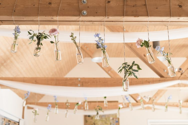 Flowers in Milk Bottles Hanging from Beams | Morris Minor Wedding Car, Hanging Flowers in Bottles and Town Crier for Village Hall Wedding in Rye | Eleanor Jane Photography