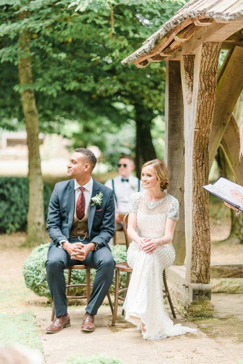 Bride in Beaded Wedding Dress and Groom in Dark Suit & Check Waistcoat at Outdoor Wedding Ceremony