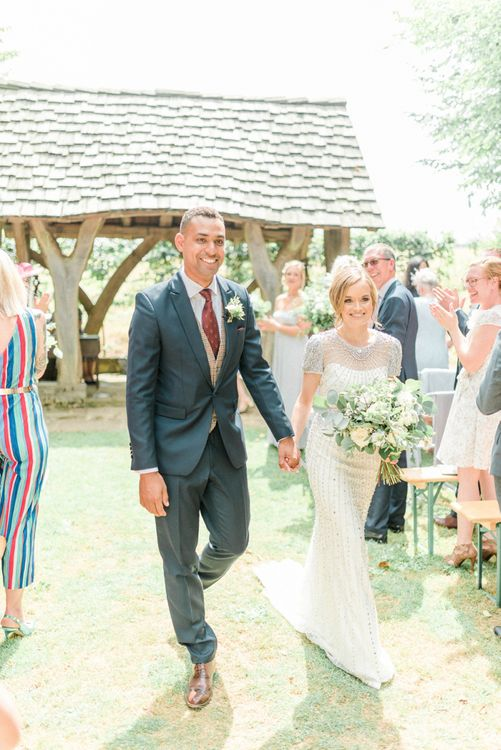 Bride in Beaded Wedding Dress and Groom in Dark Suit & Check Waistcoat Walking Up The Aisle as Husband  and Wife
