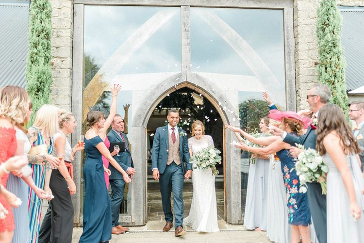 Confetti Moment with Bride in Beaded Wedding Dress and Groom in Dark Suit & Check Waistcoat