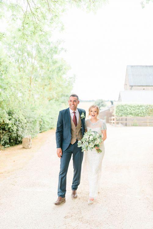 Happy Bride in Beaded Wedding Dress and Groom in Dark Suit & Check Waistcoat