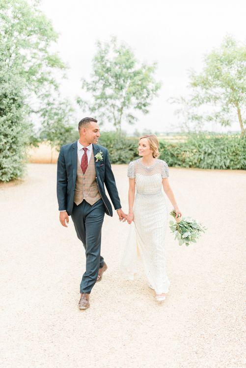 Bride in Beaded Wedding Dress and Groom in Dark Suit & Check Waistcoat Holding Hands