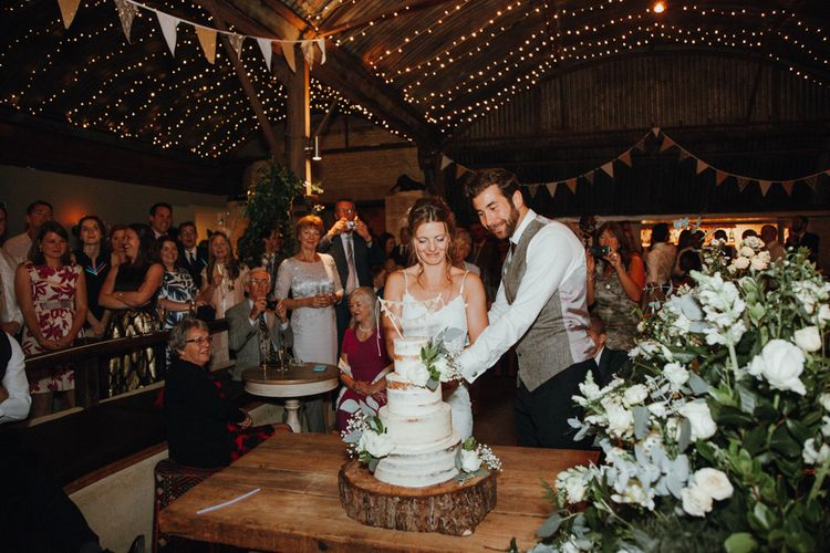 Cutting The Cake // Glastonbury Themed Table Plan For Wedding At Stone Barn Cotwolds With Groom In Cad & The Dandy Images Meghan Lorna