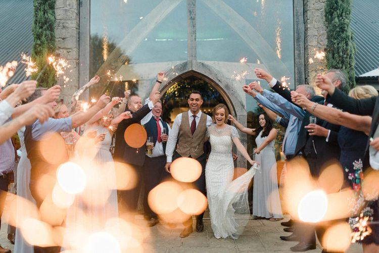 Sparkler Exit Bride in Beaded Wedding Dress and Groom in Dark Suit & Check Waistcoat