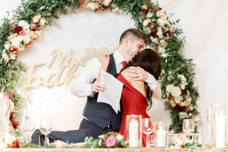 Wedding Reception Speeches   Floral Hoop   Top Table Decor   Bride in Bespoke Red Gown from agape Bridal Boutique   Groom in Slaters Suit   Red New Years Eve Winter Wedding at Iscoyd Park, Shropshire   White Stag Wedding Photography   Lovetwofilm