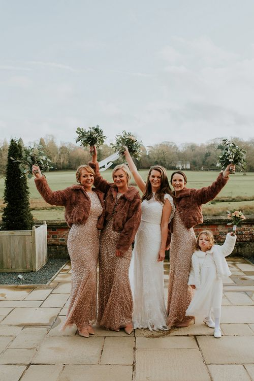 Bridesmaids in sequin dresses with cover-ups for winter wedding