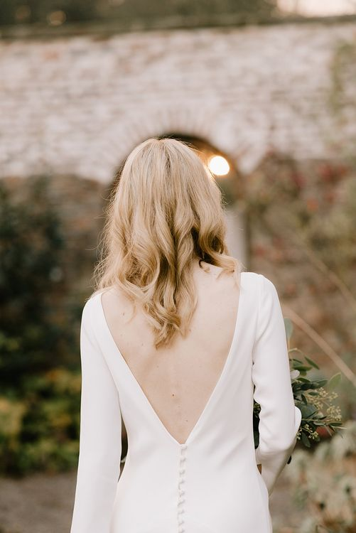 Bride in Long Sleeved Andrea Hawkes Dress with Bateau Neck and Low V-Back with Buttons | Bridal Bouquet with Eucalyptus, White Roses, White and Blue Thistles and Ferns | Emerald Green Bridesmaid Dress for a Winter Wedding at Middleton Lodge | Georgina Harrison Photography