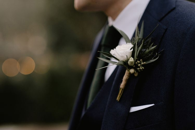 Groom in Navy Three-Piece Suit from Suit Supply with Green Tie | Buttonhole of Eucalyptus, Thistle and White Rose | Emerald Green Bridesmaid Dress for a Winter Wedding at Middleton Lodge | Georgina Harrison Photography