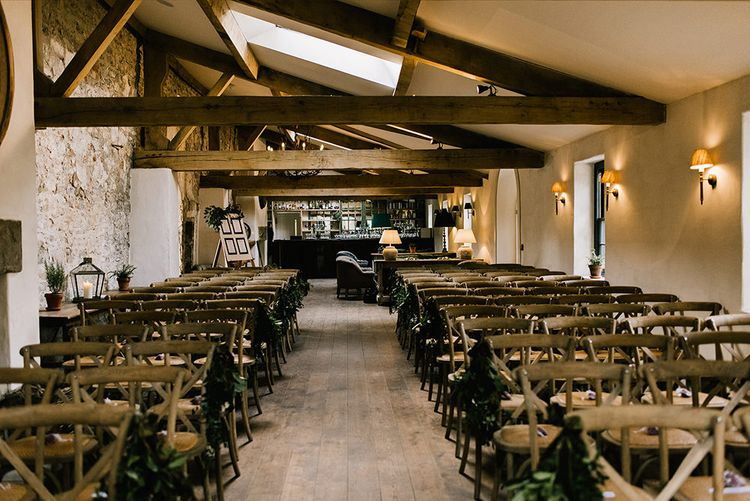 Foliage Pew Ends | Rustic Wooden Chairs | Wedding Ceremony in The Boiler House Bar at Middleton Lodge | Emerald Green Bridesmaid Dress for a Winter Wedding at Middleton Lodge | Georgina Harrison Photography