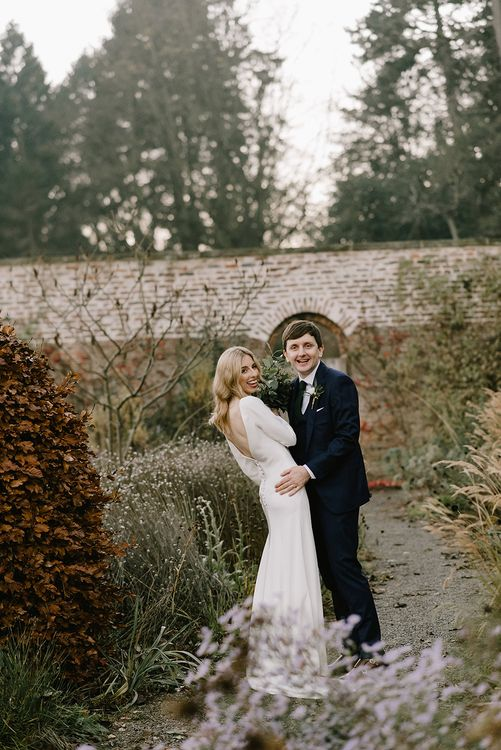 Bride in Long Sleeved Andrea Hawkes Dress with Bateau Neck and Low V-Back with Buttons | Groom in Navy Three-Piece Suit from Suit Supply with Green Tie | Bridal Bouquet with Eucalyptus, White Roses, White and Blue Thistles and Ferns | Emerald Green Bridesmaid Dress for a Winter Wedding at Middleton Lodge | Georgina Harrison Photography