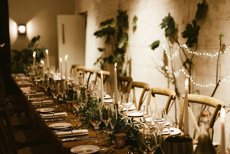 Wooden Banquet Tables | Foliage Table Runners | White Tapered Candles | Gold Candlesticks | Gold Tea Light Holders | Emerald Green Bridesmaid Dress for a Winter Wedding at Middleton Lodge | Georgina Harrison Photography