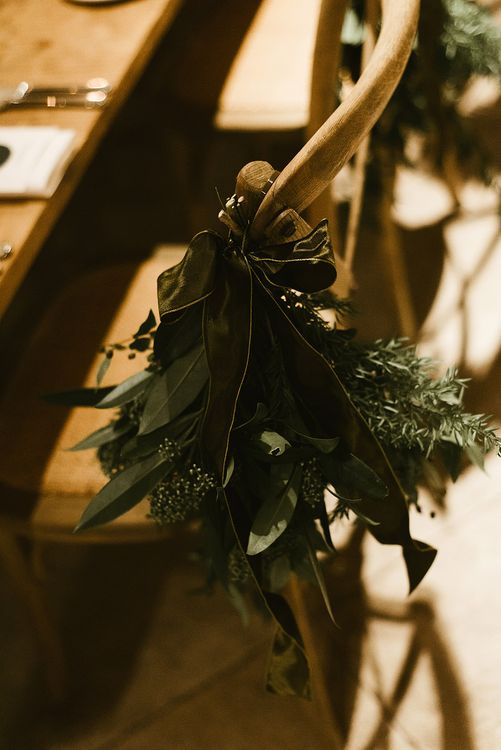 Foliage Chair Accessory Tied with Green Ribbon | Emerald Green Bridesmaid Dress for a Winter Wedding at Middleton Lodge | Georgina Harrison Photography
