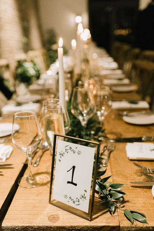Table Number in Gold Frame | Wooden Banquet Tables | Foliage Table Runners | White Tapered Candles | Emerald Green Bridesmaid Dress for a Winter Wedding at Middleton Lodge | Georgina Harrison Photography