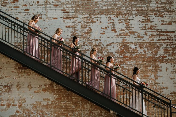 Bridal Party on Staircase at BRIK | Bride in Sleeveless High-Neck Stella York Gown with Lace Overlay and Gold Underskirt | Bridesmaids in Pink Dresses with Lace Bodice | Colourful Bouquets of Pink, Orange and White Flowers with Ferns, Eucalyptus and Greenery | Rifle Paper Co. Trainers for Informal Wedding in Fort Worth, Texas | Paul & Nanda Photography