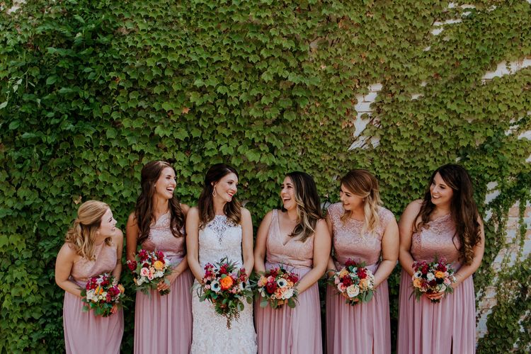Bride in Sleeveless High-Neck Stella York Gown with Lace Overlay and Gold Underskirt | Bridesmaids in Pink Dresses with Lace Bodice | Colourful Bouquets of Pink, Orange and White Flowers with Ferns, Eucalyptus and Greenery | Rifle Paper Co. Trainers for Informal Wedding in Fort Worth, Texas | Paul & Nanda Photography