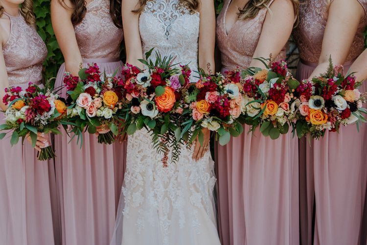 Colourful Bouquets of Pink, Orange and White Flowers with Ferns, Eucalyptus and Greenery | Bride in Sleeveless High-Neck Stella York Gown with Lace Overlay and Gold Underskirt | Bridesmaids in Pink Dresses with Lace Bodice | Rifle Paper Co. Trainers for Informal Wedding in Fort Worth, Texas | Paul & Nanda Photography