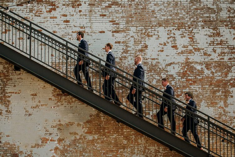 Groom's Party on Staircase at BRIK | Groom in Navy Suit and Floral Tie | Groomsmen in Navy Suits and Silk Blush Ties | Rifle Paper Co. Trainers for Informal Wedding in Fort Worth, Texas | Paul & Nanda Photography