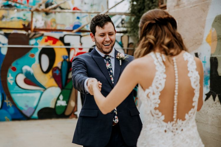 First Look Photo | Bride in Sleeveless High-Neck Stella York Gown with Lace Overlay and Gold Underskirt | Groom in Navy Suit and Floral Tie | Rifle Paper Co. Trainers for Informal Wedding in Fort Worth, Texas | Paul & Nanda Photography